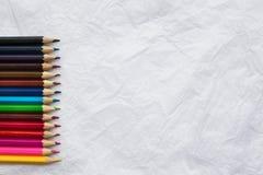 Lápis coloridos na folha branca amarrotada Fotografia de Stock