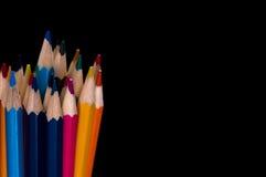 Lápis coloridos no canto de inferior esquerdo em um fundo preto Imagem de Stock Royalty Free