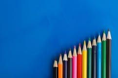 Lápis coloridos no fundo azul Foto de Stock Royalty Free