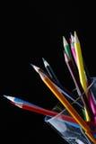 Lápis coloridos no fundo preto de vidro desobstruído Imagens de Stock Royalty Free