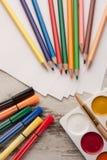 Lápis coloridos no papel com canetas com ponta de feltro e aquarela ao lado fotos de stock royalty free