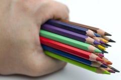 Lápis coloridos terra arrendada da mão imagens de stock