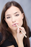 Lápis cosmético nos bordos da mulher, foco nos bordos Fotos de Stock Royalty Free