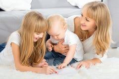 Lápis da cor da mãe e da tração das crianças em casa fotografia de stock royalty free