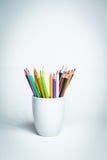 Lápis da cor em uma caneca branca Imagem de Stock