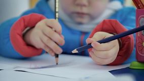 Lápis da cor nas mãos de uma criança filme
