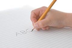 Lápis da terra arrendada da mão da criança, alfabeto da escrita no papel Fotografia de Stock Royalty Free