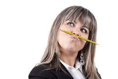 Lápis da terra arrendada da mulher de negócios na boca Fotografia de Stock