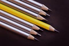 Lápis de ligação diferente de outro em um fundo preto fotos de stock