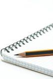 Lápis de madeira afiado no caderno da escola acima do backgroun branco fotografia de stock