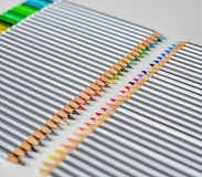 Lápis de madeira coloridos que encontram-se em seguido isolado no fundo branco Imagens de Stock Royalty Free
