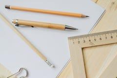 Lápis de madeira, pena, triângulo, grampo mais briefpapier na mesa na luz do dia Tabela do escritório fotos de stock royalty free