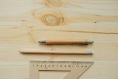 Lápis de madeira, pena, triângulo na mesa na luz do dia imagem de stock