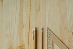 Lápis de madeira, pena, triângulo na mesa na luz do dia fotografia de stock