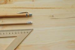 Lápis de madeira, pena, triângulo na mesa na luz do dia foto de stock royalty free