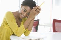 Lápis de With Notepad And da mulher de negócios que senta-se na tabela Fotografia de Stock