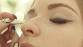 Lápis de olho preto tocante do maquilhador à mulher da pálpebra com olhos fechados Feche acima do visagist usando o lápis do lápi vídeos de arquivo