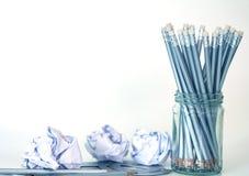 lápis de prata no frasco de vidro com o papel amarrotado na parte traseira do branco Fotos de Stock Royalty Free