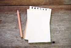 Lápis do livro de nota na madeira velha Imagem de Stock Royalty Free