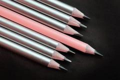 lápis do rosa da ligação diferente de outro lápis de prata em um fundo preto imagem de stock royalty free