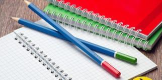 Lápis dois e um caderno aberto na tabela Fotos de Stock Royalty Free