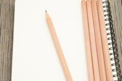 Lápis e caderno na mesa Imagem de Stock