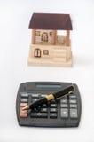 Lápis e calculadora com casa de madeira Foto de Stock Royalty Free