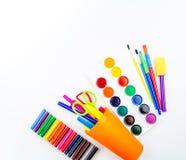 Lápis e canetas com ponta de feltro em um copo plástico, em umas pinturas e em uns pastéis pasteis em um fundo branco foto de stock