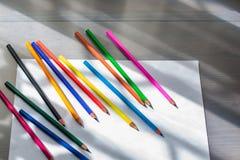 Lápis e Livro Branco coloridos foto de stock royalty free