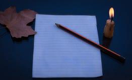 Lápis e papel iluminados pela luz de vela Imagem de Stock