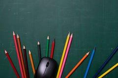 Lápis e rato coloridos do computador na mesa imagens de stock royalty free