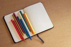 Lápis em um bloco de notas aberto com as folhas brancas vazias no papel marrom do ofício fotos de stock royalty free
