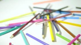 Lápis em um fundo branco Câmera no movimento Os lápis coloridos estão em uma maneira caótica video estoque
