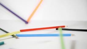 Lápis em um fundo branco Lápis colorindo que caem no fundo branco no movimento lento vídeos de arquivo