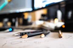 Lápis em uma mesa, perto dos monitores do computador e de um esboço foto de stock