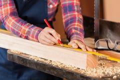 Lápis fêmea de Marking Wood With do carpinteiro foto de stock royalty free