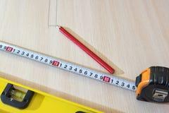 Lápis, fita métrica, construindo ao nível na superfície de madeira fotografia de stock