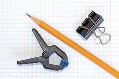 Lápis, grampo e aperto de madeira amarelos no papel quadriculado do livro de exercício, no DIY e no conceito do ofício foto de stock royalty free