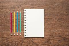 Lápis multicoloridos com o livro de nota vazio no fundo de madeira Fotografia de Stock