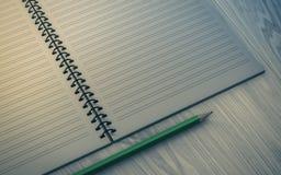Lápis no caderno verificado no fundo de madeira Imagens de Stock Royalty Free