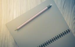 Lápis no caderno verificado no fundo de madeira Imagens de Stock