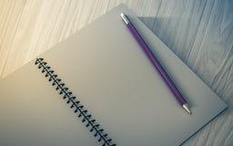 Lápis no caderno verificado no fundo de madeira Foto de Stock Royalty Free