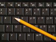 Lápis no teclado de computador Imagens de Stock Royalty Free