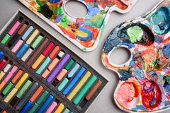 Lápis pasteis coloridos e uma paleta com pinturas na mesa do ` s do artista criação Fotografia de Stock Royalty Free