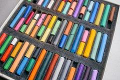 Lápis pasteis coloridos em uma caixa em uma luz - fundo cinzento Fotos de Stock