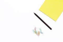 Lápis preto, clipes de papel coloridos e um bloco de notas amarelo Desktop mínimo do conceito no escritório Fotos de Stock Royalty Free