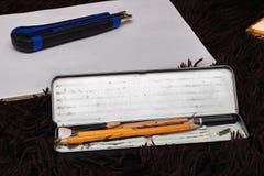 Lápis simples velhos em uma caixa do metal e em uma folha fotos de stock royalty free