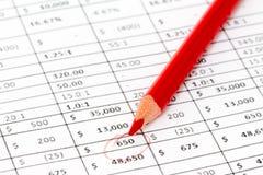 Lápis vermelho em um relatório com muitos dígitos imagem de stock royalty free