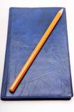 Lápiz amarillo en un diario azul Imagen de archivo libre de regalías