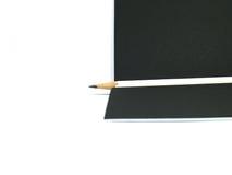 Lápiz blanco en el papel negro Foto de archivo libre de regalías
